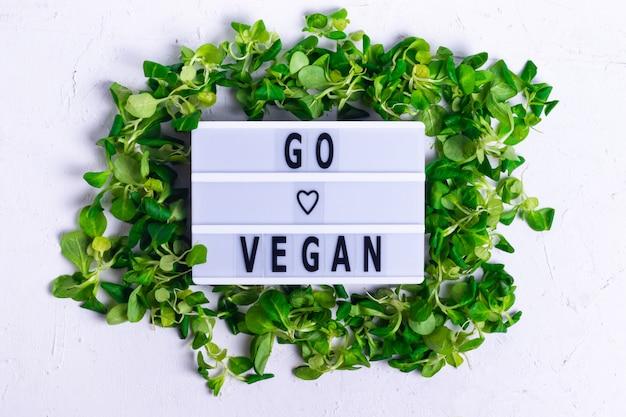 Inschrijving veganistisch in een frame van groene maïssalade op een witte gestructureerde achtergrond Premium Foto