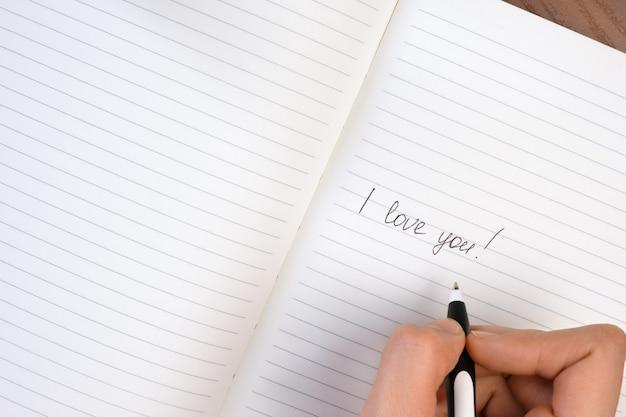 Inscriptie ik hou van je geschreven op gelinieerd notitieblok Gratis Foto