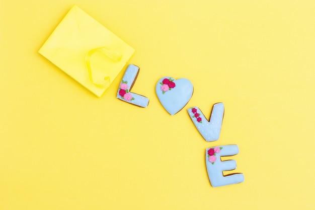 Inscriptie liefde door zelfgemaakte koekjes met blauwe suikerglazuur op geel Premium Foto