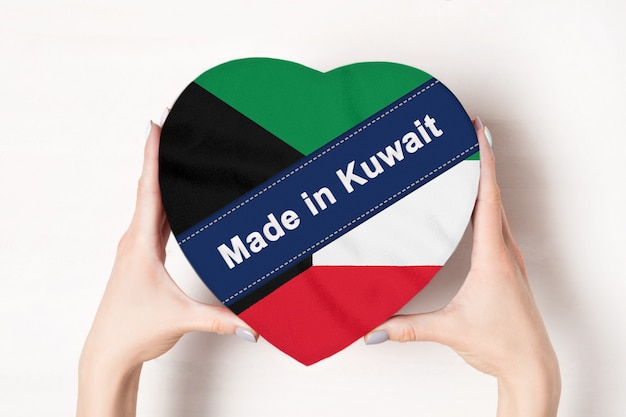 Inscriptie made in koeweit, de vlag van koeweit. vrouwelijke handen met een hartvormige doos. Premium Foto