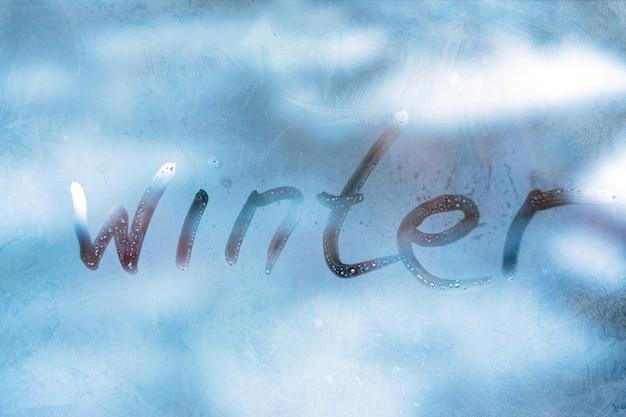Inscriptie woord winter op het blauwe glazen venster Premium Foto