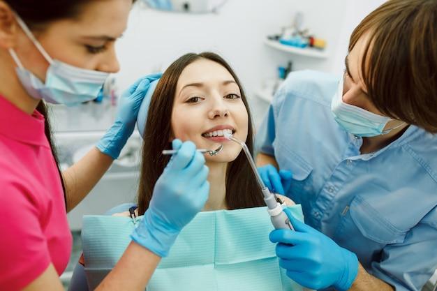 Inspectie van de tanden van de vrouw met behulp van een spiegel. Gratis Foto