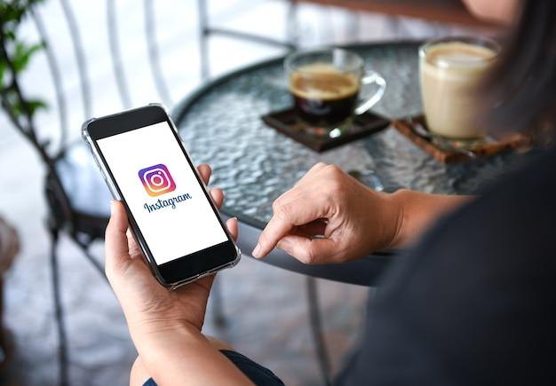 Instagram-applicatie op slimme telefoon display in de hand met koffie op tafel achtergrond Premium Foto