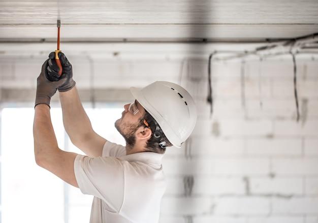 Installateur van elektricien met een gereedschap in zijn handen, werken met kabel op de bouwplaats Gratis Foto