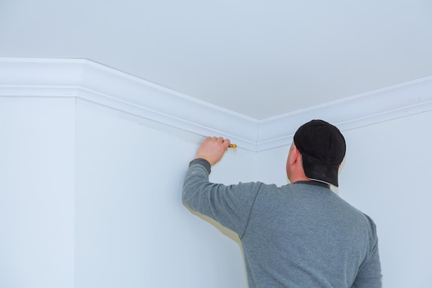 Installatie van plafondlijsten. de arbeider maakt de houtafgietsel aan het plafond Premium Foto