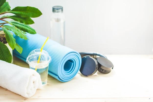 Instellen voor sport. blauwe yoga mat handdoek koptelefoon en een fles water op een licht Premium Foto