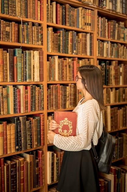 Intelligente vrouw met boek in de bibliotheek Gratis Foto