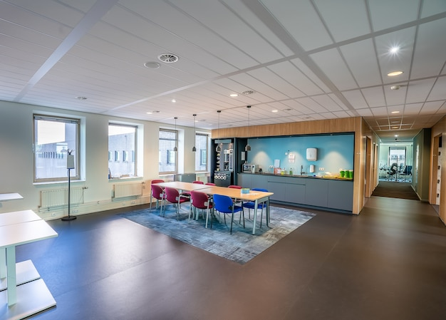 Interieur van de keuken van een modern kantoor met een lange houten tafel en stoelen Gratis Foto