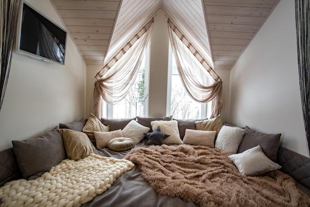 Interieur van een modern huis ruime hal met grote zachte rustplaats. eigentijdse brede bank met veel kussens en licht raam onder houten zolderplafond. Premium Foto