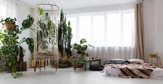 Interieur van een modern studio-appartement met veel planten en een bed op de vloer Premium Foto