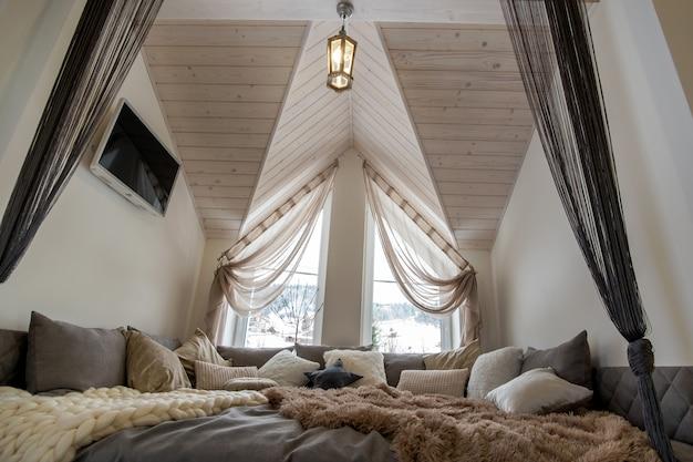 Interieur van een moderne woning ruime hal met grote zachte rustplaats. eigentijdse brede bank met veel kussens en licht raam onder houten zolderplafond. Premium Foto