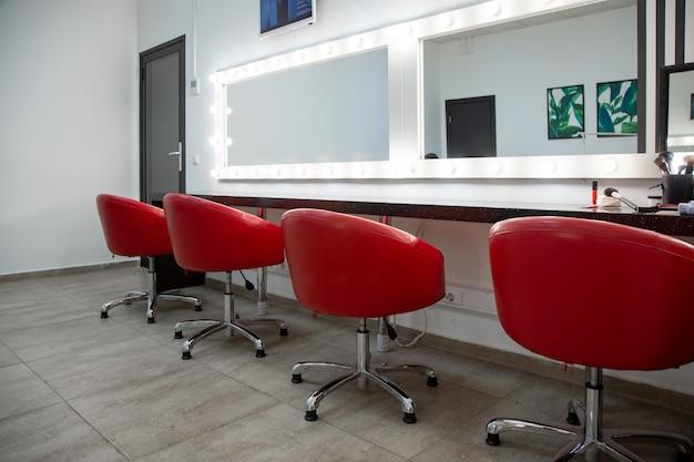 Interieur van een schoonheidssalon met rode stoelen en spiegels Premium Foto
