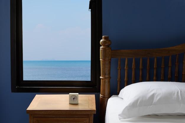 Interieur witte kussens en beddengoed in blauwe slaapkamer met uitzicht op zee in de zomer in de ochtend Premium Foto