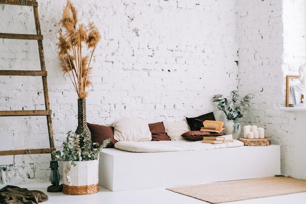 Interieurontwerp van lichte woonkamer met witte muren en bankbank met kussens Premium Foto
