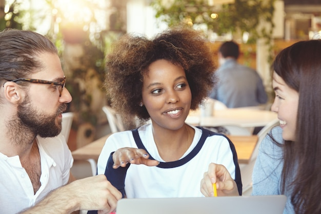 Internationaal team. multi-etnische groep partners die plannen en strategie van hun start-up bespreken. Gratis Foto