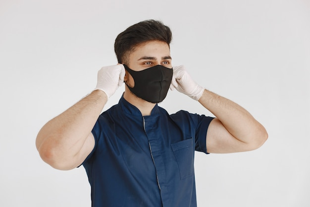 Internationale medische student. man in een blauw uniform. arts met een masker. Gratis Foto