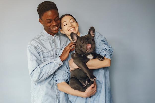 Internationale paar op een blauwe achtergrond met een hond Gratis Foto