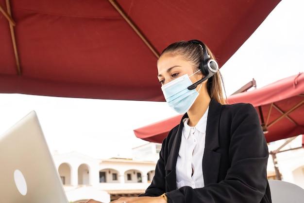 Internet freelance baankeuze concept: een jonge schattige vrouw met draadloze koptelefoon werkt op haar laptop met een medisch masker op een tafel van een bar - nieuwe normale banen met externe verbindingen en covid 19 Premium Foto
