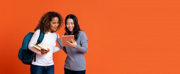 Interracial studentenvrienden die tabletcomputer bekijken Premium Foto