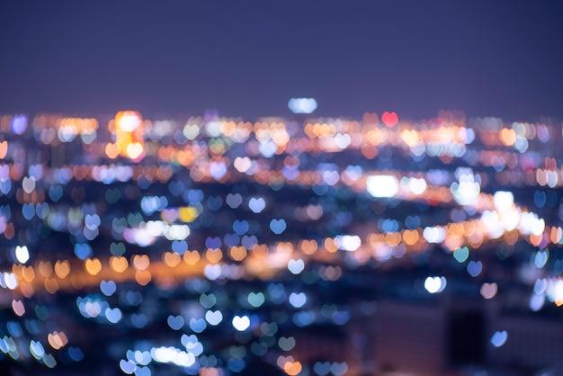 Intreepupil hartvormige oranje, blauwe en gouden lichten wazig bokeh. feestelijke zwarte kerstmis of nieuwjaar en valentijnskaartachtergrond. Premium Foto