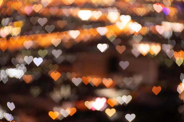 Intreepupil hartvormige oranje en gouden lichten wazig bokeh. feestelijke zwarte kerstmis of nieuwjaar en valentijnskaartachtergrond. Premium Foto