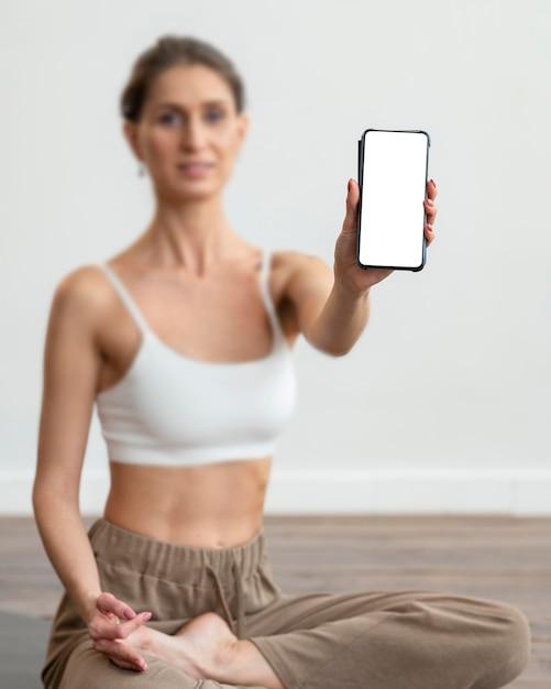 Intreepupil vrouw thuis doen yoga en smartphone te houden Gratis Foto