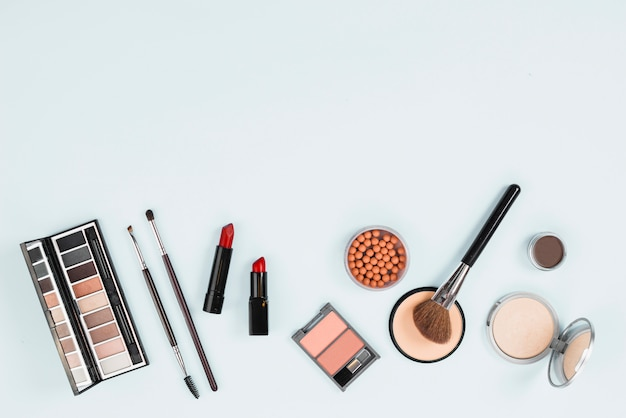 Inzameling van make-uptoebehoren op lichte achtergrond Gratis Foto