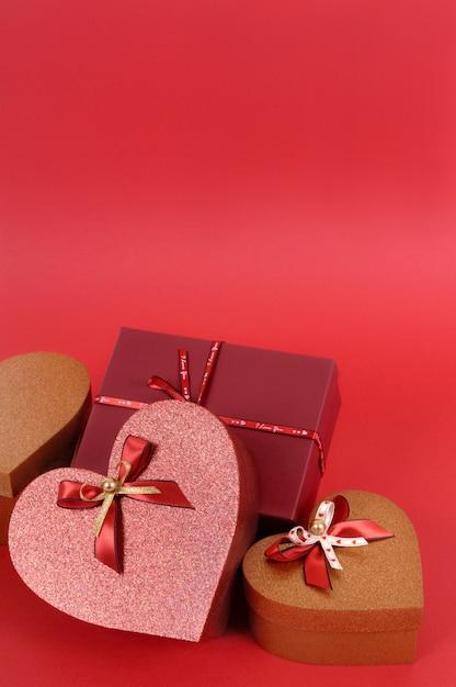Inzameling van rode en gouden valentijnskaartgiften op een rode document achtergrond. Gratis Foto
