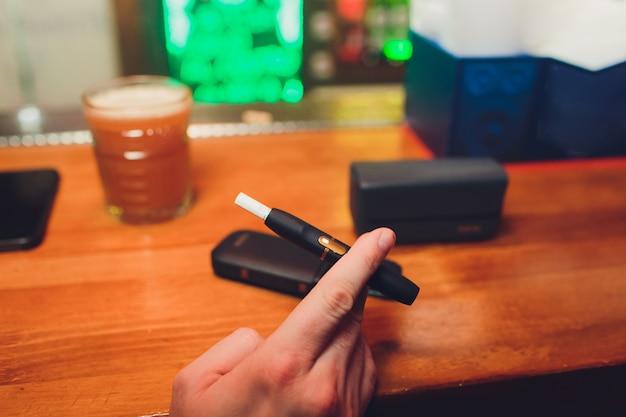 Iqos technologie voor warmte-niet-verbrand tabaksproducten. mens die e-sigaret in zijn hand houdt alvorens te roken. Premium Foto