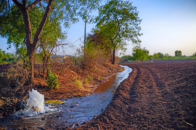 Irrigatiewaterstroom van pijp naar kanaal voor landbouwvelden, slow motion waterflits Premium Foto