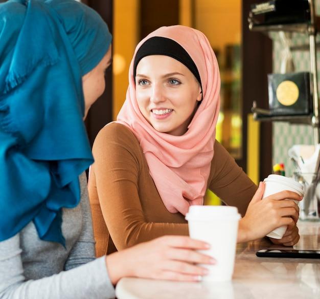 Islamitische vrouwenvrienden die en in de koffiewinkel genieten van spreken Gratis Foto