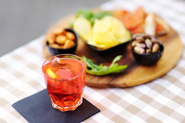 Italiaans aperitief / aperitief: glas cocktail (mousserende wijn met aperol) en aperitiefschotel op tafel Premium Foto