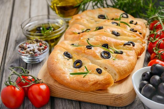 Italiaans focacciabrood met olijven en rozemarijn op rustieke houten achtergrond. Premium Foto