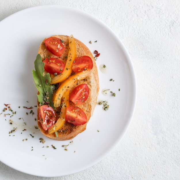 Italiaanse bruschetta met tomaten op een witte plaat tegen witte achtergrond. uitzicht van boven Premium Foto