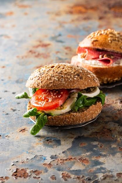 Italiaanse caprese sandwiches met verse tomaten, mozzarella kaas en veldsla, meergranenbroodje Premium Foto