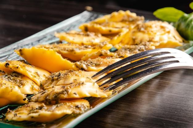 Italiaanse gevulde pasta ravioli met pestosaus Premium Foto