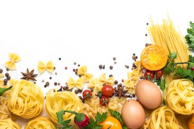 Italiaanse pasta van verschillende soorten met kruiden, rode peper, kippeneieren op een witte achtergrond. Premium Foto