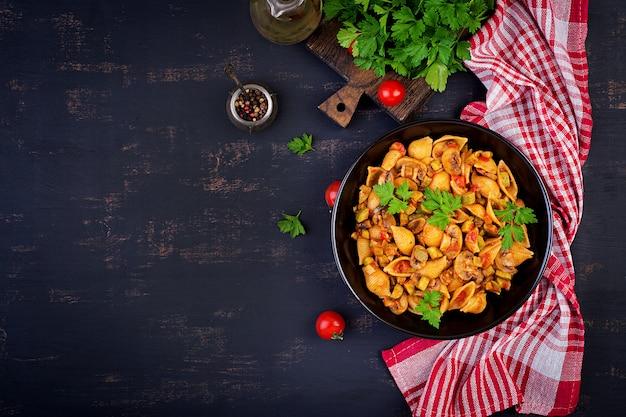 Italiaanse pastaschelpen met champignons, courgette en tomatensaus Premium Foto