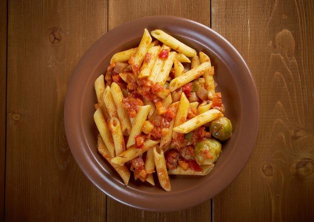 Italiaanse penne rigate pasta met plantaardige tomatensaus op houten tafel Premium Foto