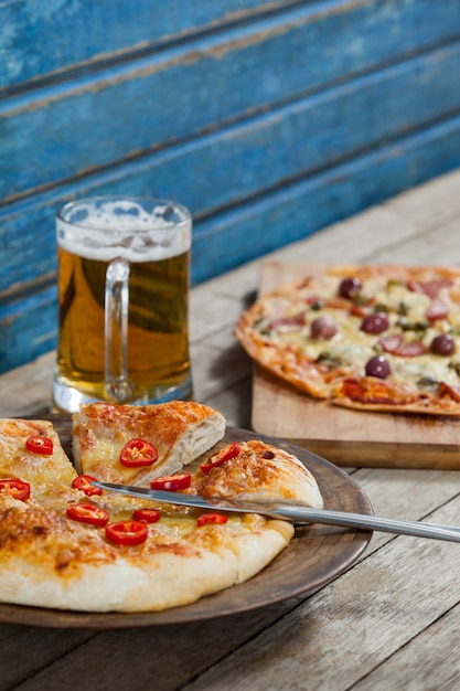Italiaanse pizza geserveerd met glas bier op houten plank Premium Foto