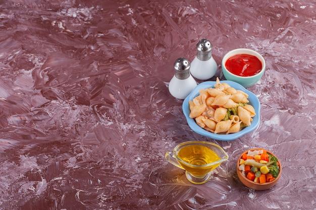 Italiaanse shell pasta met tomatensaus en gemengde groentesalade op lichte tafel. Gratis Foto