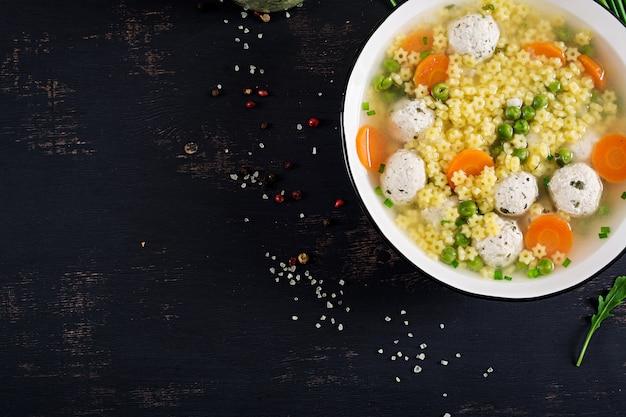 Italiaanse vleesballensoep en stelline-gluten vrije deegwaren in kom op zwarte lijst. Gratis Foto
