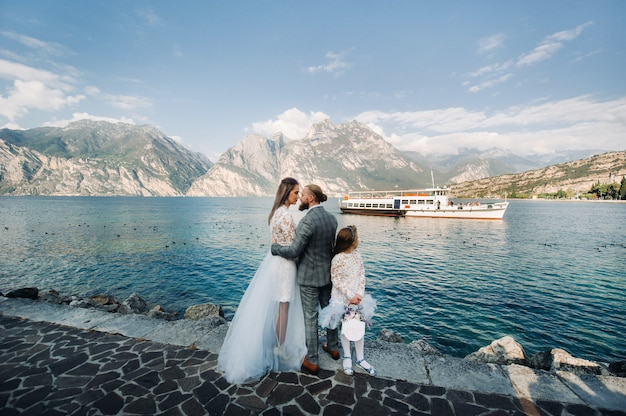 Italië, gardameer. prachtige familie aan de oevers van het gardameer in italië aan de voet van de alpen. vader, moeder en dochter in italië. Premium Foto