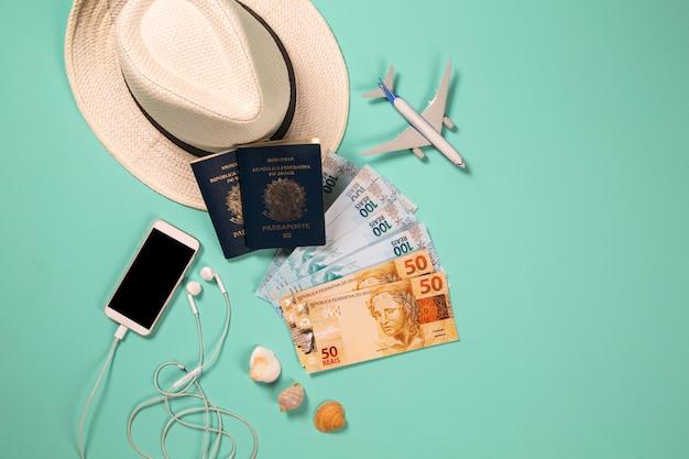 Items voor zomervakantie: telefoon, paspoort, geld en vliegtuig. blauwe achtergrond, bovenaanzicht Premium Foto