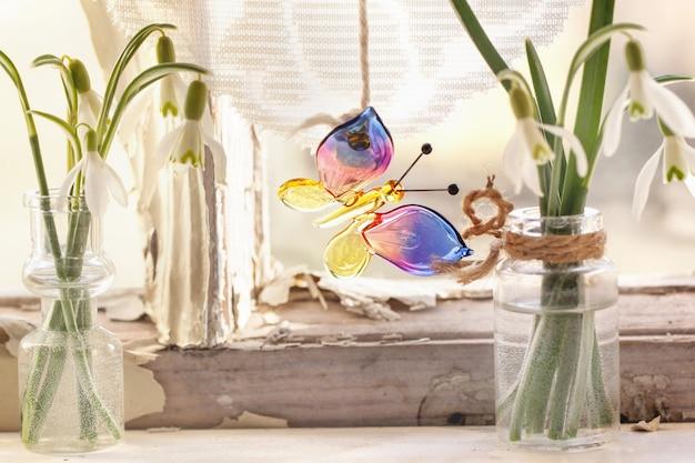 Iterieur venster met glazen vlinder en sneeuwklokjes Premium Foto