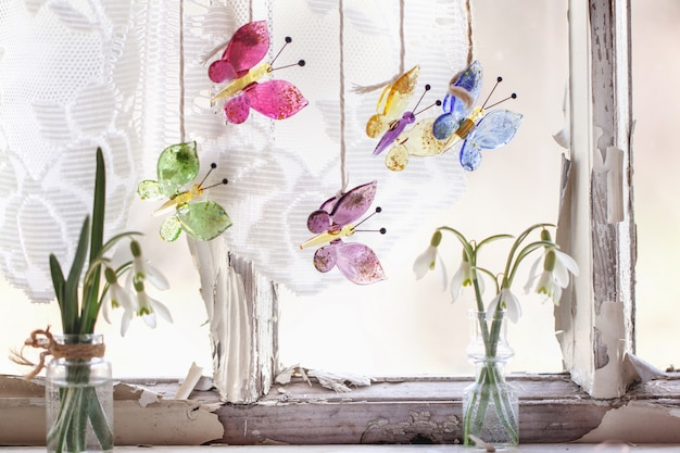Iterieur venster met glazen vlinders en sneeuwklokjes Premium Foto