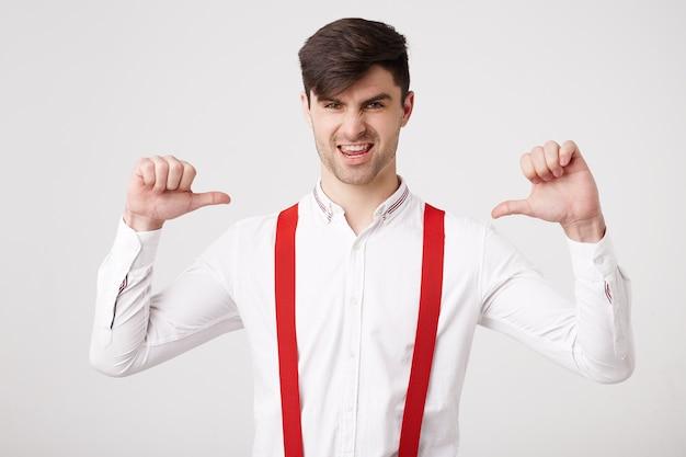 Ja, ik ben een winnaar! zelfverzekerde jonge man heeft iets belangrijks gedaan, wil blikken ontvangen die met de duim naar zichzelf wijzen, voelt zich een winnaar, leider, succesvolle man, draagt een wit overhemd Gratis Foto