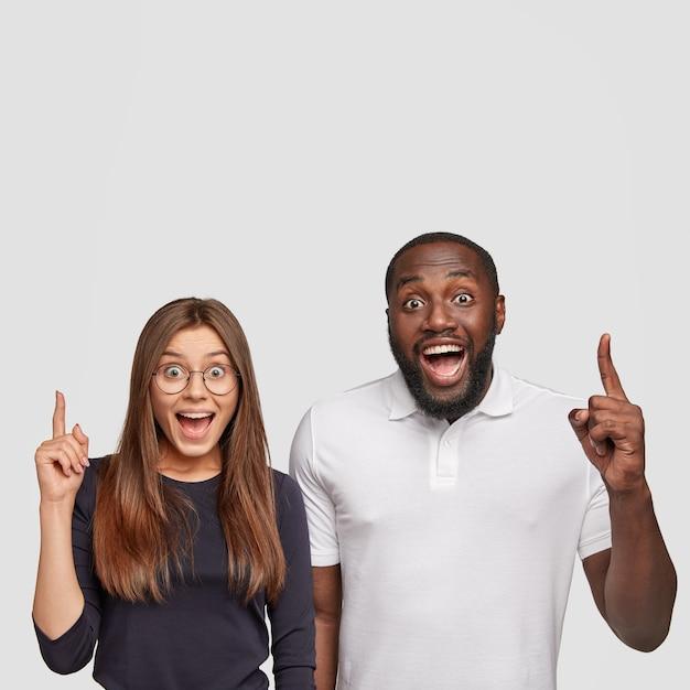 Ja, kijk gewoon naar boven! tevreden donkere jonge man en europese vrouw wijzen met wijsvingers erboven Gratis Foto