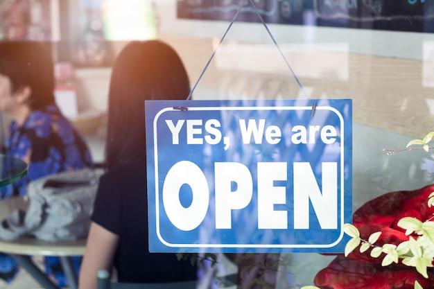 Ja, we zijn open teken opknoping op de deur van het café. Premium Foto