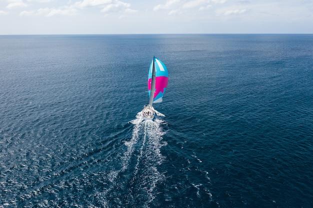Jacht met een kleurrijk zeil in de zee Premium Foto